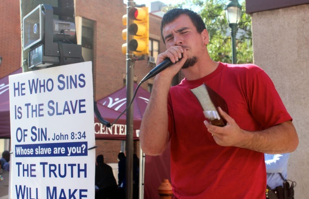A street protestor preaches against homosexuality at Philadelphia's Outfest 2013.  Photo by Isaac Riddle.